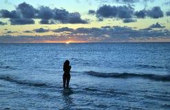 A menina bonita fotografa o por do sol das caraíbas Fotografia de Stock Royalty Free