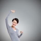 A menina bonita gesticula os punhos triunfais Fotografia de Stock