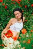Menina bonita grávida no campo da papoila Foto de Stock