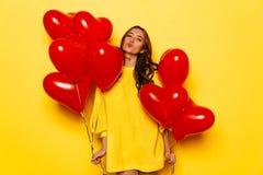 A menina bonita guarda balões vermelhos em duas mãos no dia do ` s do Valentim foto de stock