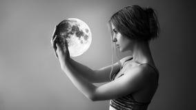 A menina bonita guarda a lua Imagem de Stock Royalty Free