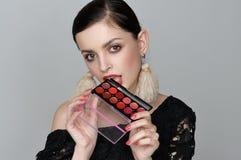 A menina bonita guarda uma paleta cosmética de cores mornas Fotos de Stock