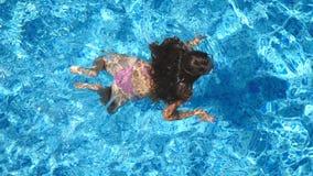 Menina bonita irreconhecível que flutua através da associação do hotel Natação da jovem mulher na água azul clara da bacia sobre video estoque