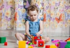 A menina bonita joga brinquedos fotografia de stock