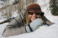 A menina bonita joga e sorri na neve Fotografia de Stock