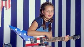 A menina bonita joga uma guitarra elétrica no estúdio A morena bonita joga a guitarra na sala clara do estúdio filme