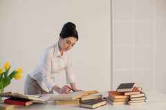 A menina bonita lê livros na tabela que prepara-se para o exame Foto de Stock