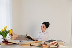 A menina bonita lê livros na tabela que prepara-se para o exame Foto de Stock Royalty Free