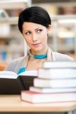 A menina bonita lê no salão da leitura fotografia de stock royalty free