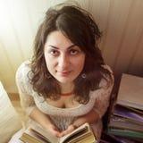 A menina bonita lê um livro pela luz da lâmpada Vista de cima para baixo Fotografia de Stock Royalty Free