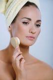A menina bonita lava a pele na face foto de stock