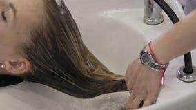 A menina bonita lava seu cabelo antes do corte de cabelo no sal?o de beleza Lavagem do cabelo filme
