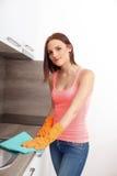 A menina bonita limpa a cozinha fotos de stock royalty free