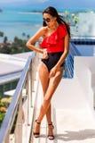 Menina bonita luxuosa em um roupa de banho marcado e em vidros, em um hotel caro em uma ilha tropical, contra um fundo dos azuis  fotografia de stock