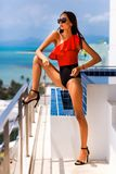 Menina bonita luxuosa em um roupa de banho marcado e em vidros, em um hotel caro em uma ilha tropical, contra um fundo dos azuis  imagens de stock royalty free