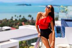 Menina bonita luxuosa em um roupa de banho marcado e em vidros, em um hotel caro em uma ilha tropical, contra um fundo dos azuis  fotos de stock royalty free
