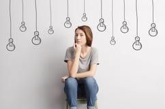Menina bonita, magro que senta-se em um tamborete e que olha seguramente Fotos de Stock