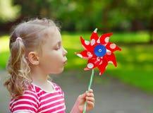 A menina bonita mantém o moinho de vento disponivel Imagens de Stock Royalty Free