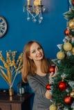 A menina bonita mesma está perto da árvore de Natal e dos brinquedos dos toques fotos de stock royalty free