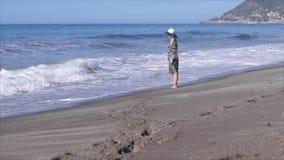 A menina bonita molha os pés no mar vídeos de arquivo