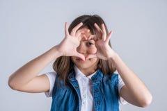 A menina bonita mostra o coração com dedos, amor fotografia de stock