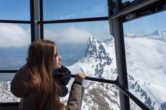 Menina bonita na cabine do teleférico, altamente acima das montanhas Vista da gôndola Imagens de Stock