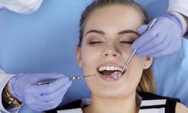 Menina bonita na cadeira dental no exame no de fotos de stock royalty free