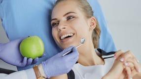 Menina bonita na cadeira dental no exame no de fotos de stock