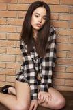 Menina bonita na camisa quadrada que levanta ao lado de uma parede de tijolo Foto de Stock Royalty Free