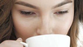 A menina bonita na camiseta bebe uma xícara de café perto da janela lentamente vídeos de arquivo
