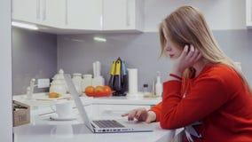 Menina bonita na camiseta vermelha usando o portátil na cozinha filme