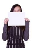Menina bonita na cozinha que prende um sinal em branco imagem de stock