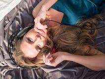 Menina bonita na escuta de sorriso da roupa de noite a música nos fones de ouvido que encontram-se na cama olhe a câmera De cima  Fotografia de Stock Royalty Free