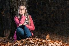 Menina bonita na floresta do outono que l? um livro a mulher senta-se perto de uma ?rvore e guarda-se um livro imagens de stock
