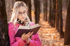 Menina bonita na floresta do outono que l? um livro suporte da mulher perto da ?rvore e para ler um livro imagens de stock royalty free