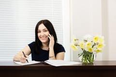 Menina bonita na mesa de recep??o que responde ? chamada no escrit?rio dental fotografia de stock