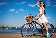 Menina bonita na praia com bicicleta do cruzador imagens de stock