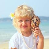 Menina bonita na praia com seashell Fotografia de Stock Royalty Free