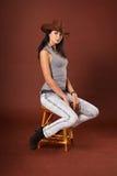 Menina bonita na roupa das calças de brim e em um chapéu de cowboy foto de stock royalty free