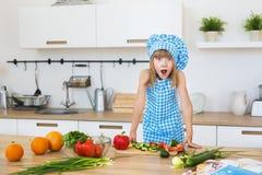 A menina bonita na roupa do cozinheiro abre seus olhos e boca em uma cozinha imagens de stock