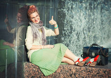 A menina bonita na roupa do vintage que mostra os polegares levanta o gesto foto de stock