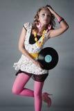 A menina bonita na tendência veste o disco do vinil da terra arrendada Imagem de Stock Royalty Free