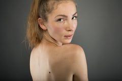 Menina bonita nas calças de brim e em um espartilho de creme Foto de Stock