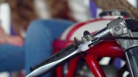 A menina bonita nas calças de brim senta-se na motocicleta Ascendente próximo da motocicleta a motocicleta vermelha no estúdio Mo vídeos de arquivo