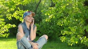 A menina bonita nas calças de brim veste a fala no telefone no parque video estoque