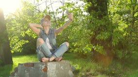 A menina bonita nas calças de brim veste a fatura do selfie no telefone no parque video estoque