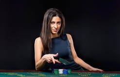 A menina bonita, negociante, atrás de uma tabela para o pôquer Fotografia de Stock Royalty Free