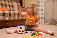 Menina bonita no assoalho com brinquedo à disposicão Foto de Stock Royalty Free