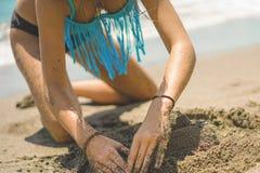A menina bonita no biquini constrói um castelo da areia na praia fotos de stock royalty free