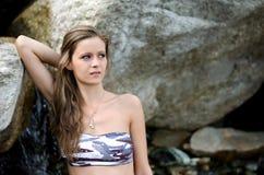 Menina bonita no biquini contra a rocha Imagens de Stock